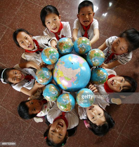 Pupils pose with globes to welcome the upcoming Earth Day at a school in Lianyuan on April 18 2017 in Loudi Hunan Province of China A school in...