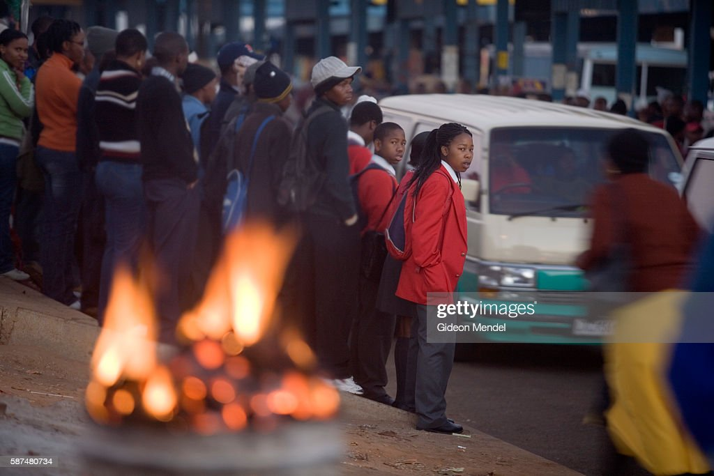 Pupils queue for transport at the Baragwanath taxi rank which will take them to their school outside of Soweto In the foreground is a a hawker's...