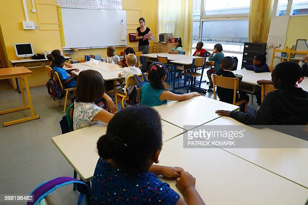 Pupils sit in a classroom as a teacher speaks during the first day of the school year at the Oran elementary school in Paris on September 1 2016...