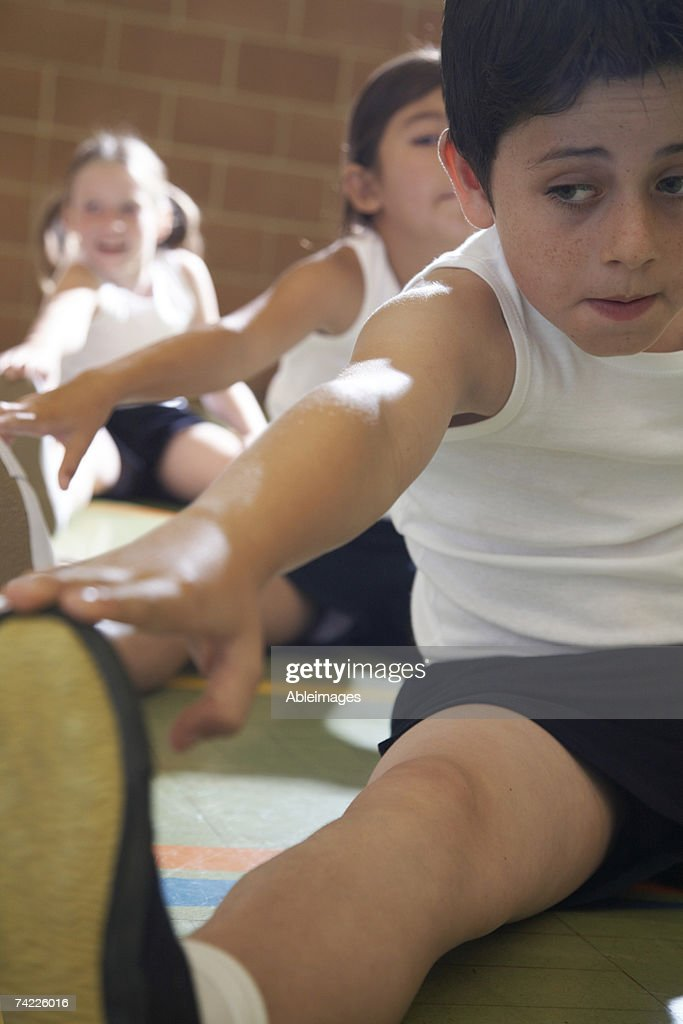 Pupils (10-11) stretching on gymnasium floor