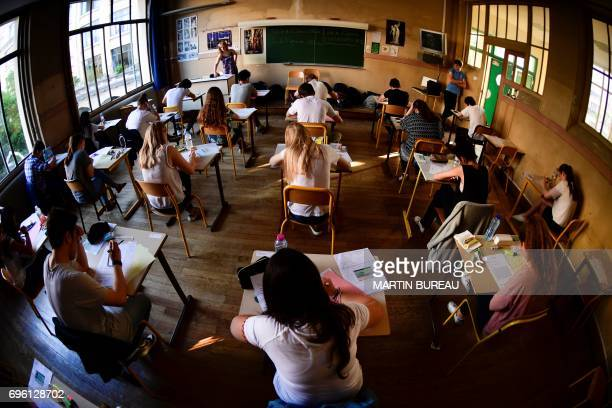 Pupils take part in the first written test in philosophy as part of the Baccalaureat at a school in Paris on June 15 2017 / AFP PHOTO / Martin BUREAU