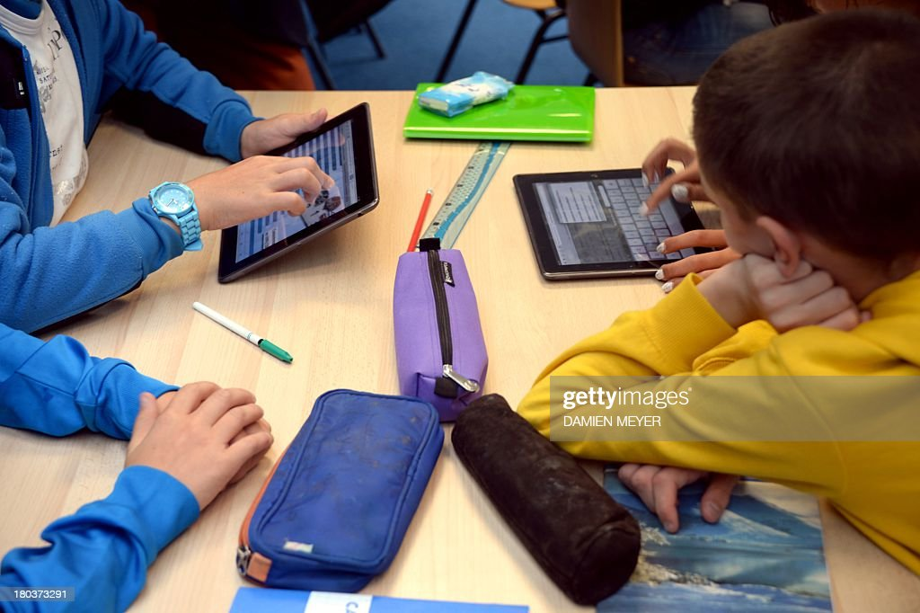 Pupils use tablets during courses in a classroom at the Leonard de Vinci 'connected' middle school in Saint-Brieuc, western France on September 12, 2013. The Leonard de Vinci school is one of the 23 middle schools in France to be connected to the internet and to be using new information technologies during courses. AFP PHOTO / DAMIEN MEYER