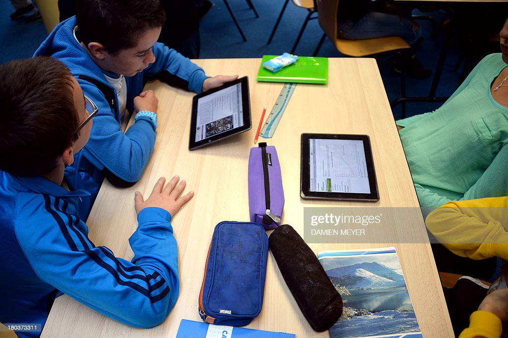 Pupils use tablets during courses in a classroom at the Leonard de Vinci 'connected' middle school in Saint-Brieuc, western France on September 12, 2013. The Leonard de Vinci school is one of the 23 middle schools in France to be connected to the internet and to be using new information technologies during courses.