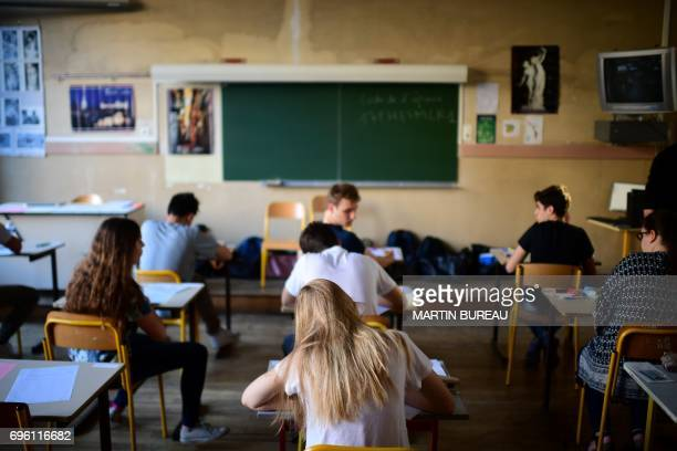 Pupils wait for the start of the first written test in philosophy as part of the Baccalaureat at a school in Paris on June 15 2017 / AFP PHOTO /...