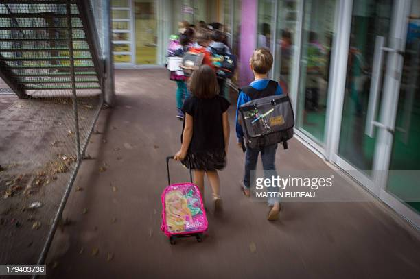 Pupils walk to their classroom in the courtyard of a primary school on September 3 2013 in Paris on the first day of school More than 12 million...