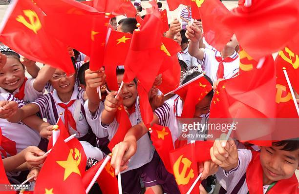 Pupils wave Chinese Communist Party flags at Yuanqian Primary School on June 30 2011 in Lianyungang Jiangsu Province of China This year's...