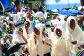 Pupils wave national flags greet Camilla Duchess of Cornwall and Prince Charles Prince of Wales as they arrive at Unguja Urban North Teacher's...