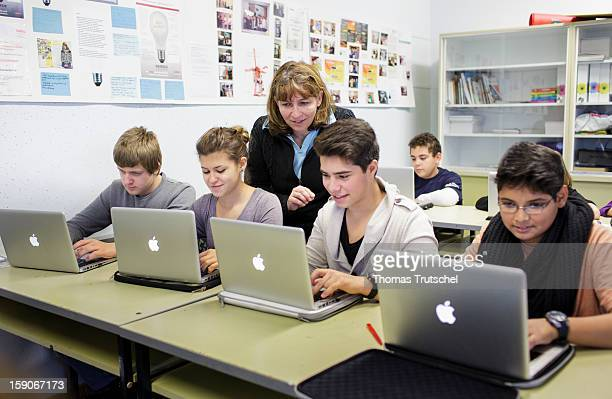 Pupils with their teacher working at their laptops during a lesson at the HeinrichMannSchool in the Neukoelln district of Berlin Germany on November...
