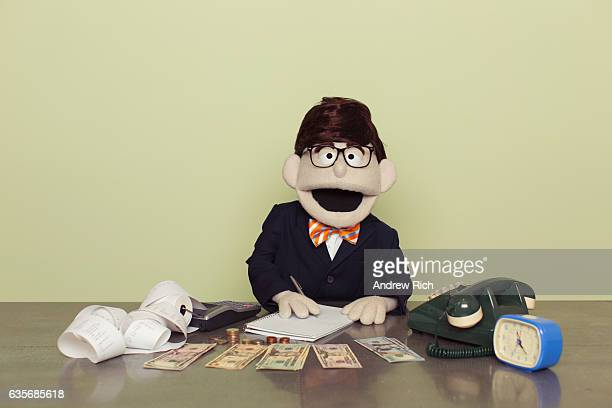 Puppet Accountant Counts American Dollars with Calculator