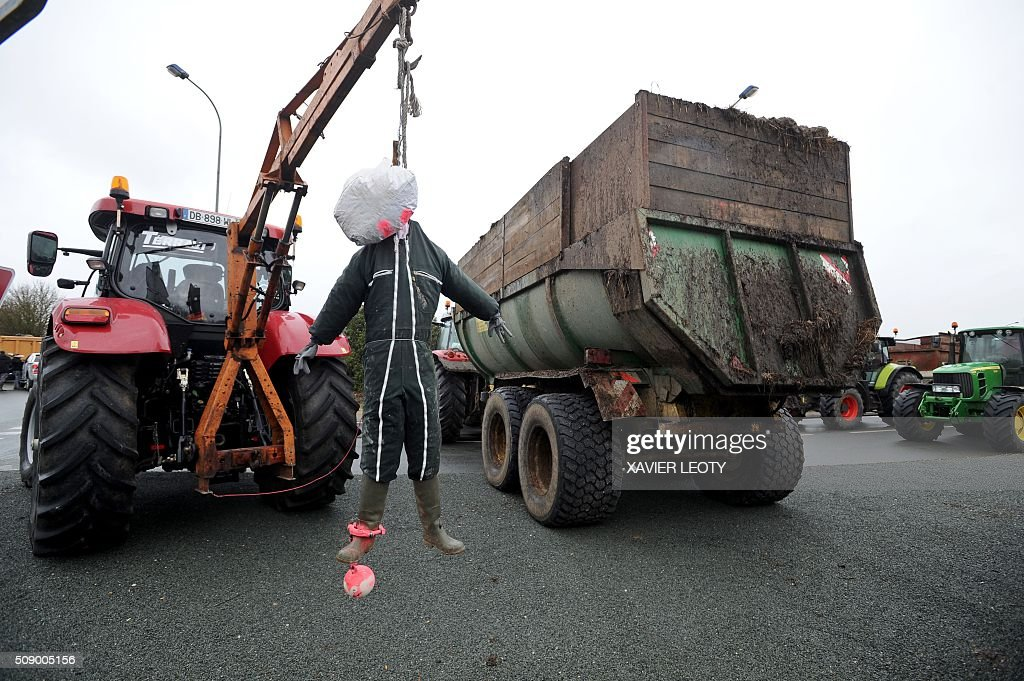 A puppet depicting a farmer hung by the neck and wearing ball and chain hangs from a tractor as farmers block a road near Saintes, western France, on February 8, 2016, during a demonstration against the purchase price of their products by supermarkets. Over 100 tractors were used by mostly pig and dairy farmers to block strategic points giving access to the city, disrupting traffic and closing an interchange of the A10 motorway. / AFP / XAVIER LEOTY