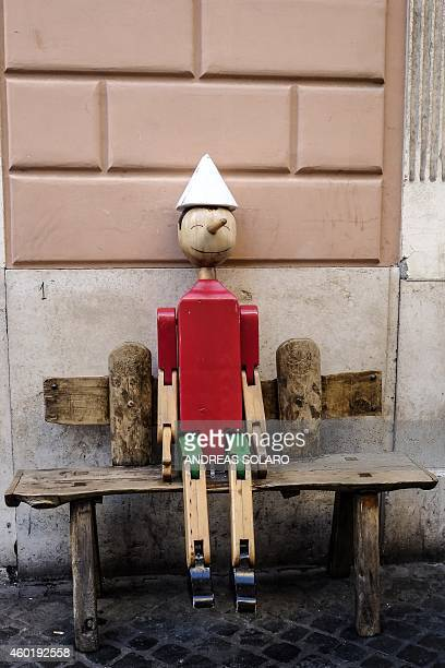 A puppet depicting Italian character Pinocchio is installed outside a shop in central Rome on December 9 2014 AFP PHOTO / ANDREAS SOLARO
