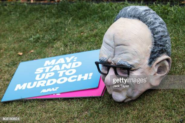 A puppet head of Australian media Mogul Rupert Murdoch sits next to placards following a photocall by campaigners from Avaaz outside the Houses of...
