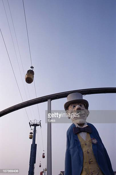 A puppet in a top hat and bow tie looms large underneath the cable cars in the seaside resort of Blackpool Lancashire August 1983