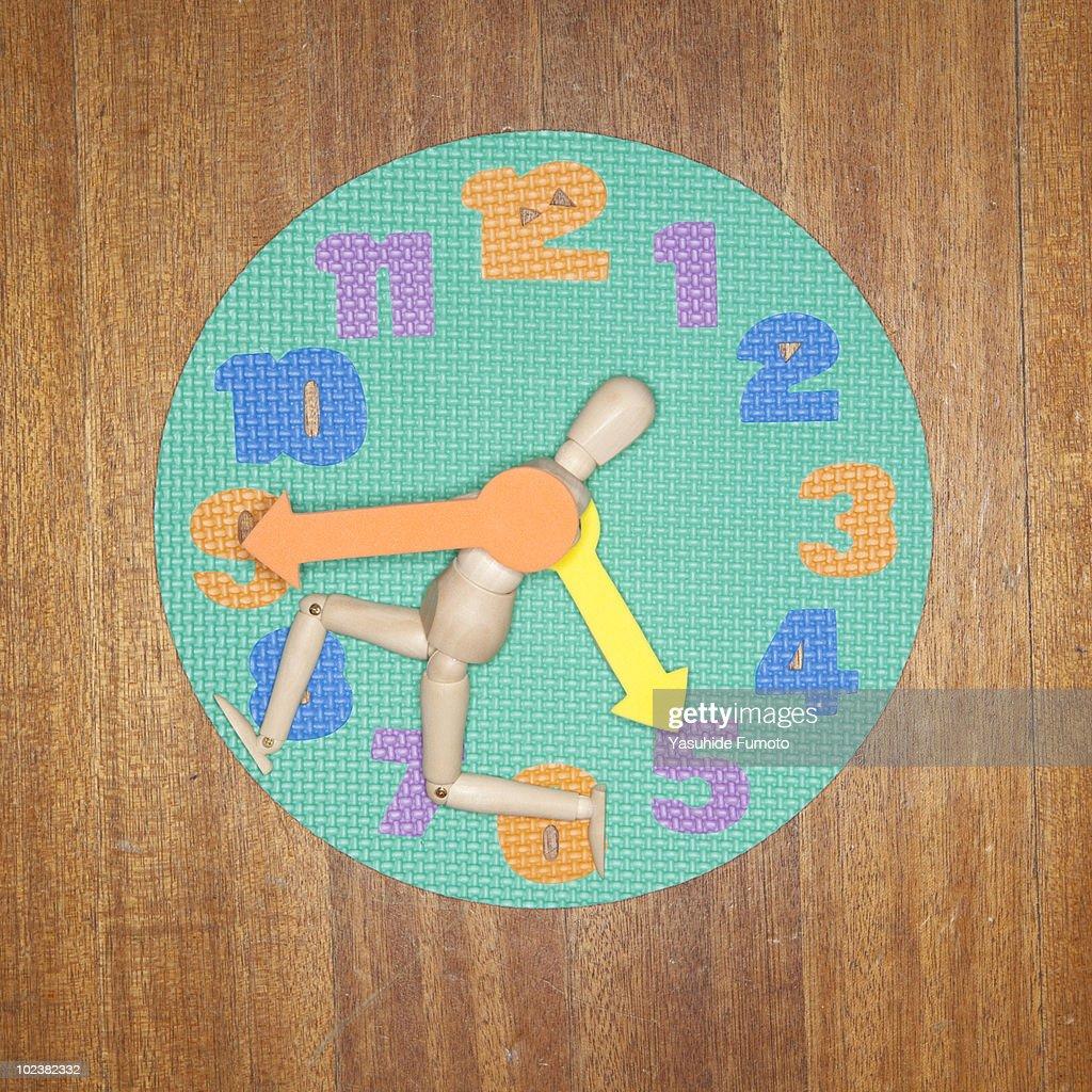 A puppet on a toy clock. : Foto de stock