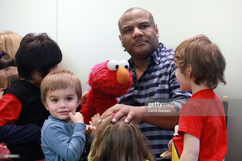 Puppeteer Kevin Clash (center) and Elmo talk at the Apple Store Upper West Side on November 20, 2011 in New York City.