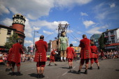 Puppeteers operate the The Little Giant Girl one of the giant Royal De Luxe street puppets taking part in Liverpool's World War I centenary...