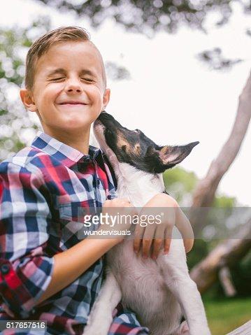 Puppy dog licking mischievous little boy's face in park