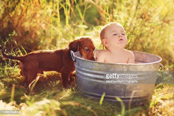 Puppy with baby in bath tub