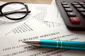 Purchase agreement document for filling and signing on desk