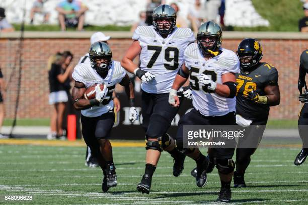 Purdue Boilermakers running back Tario Fuller left runs with the ball and some protection from Purdue Boilermakers offensive lineman Matt McCann...