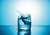 Pure water splashing out of glass on blue background