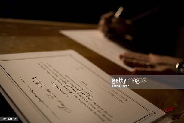A purity ring ceremony participant signs a 'True Love Waits' certificate as another form of their pledge on February 13 2008 at the Full Life...