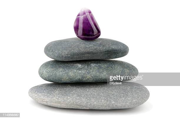 Purple Amethyst Gemstone On Piled Black Stones
