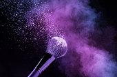 purplish blusher exploding over a cosmetic brush isolated on black background