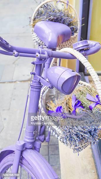 Purple bike with basket of flowers