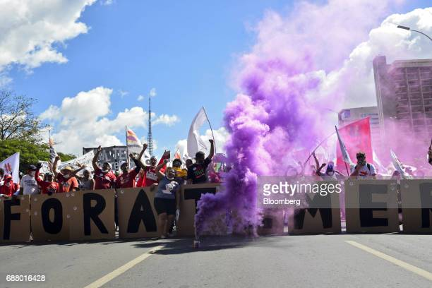 Purple colored smoke rises as demonstrators hold placards and flags during protests outside of the National Congress demanding the resignation of...