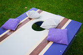 Cornhole beanbag toss wood game board outside on grass