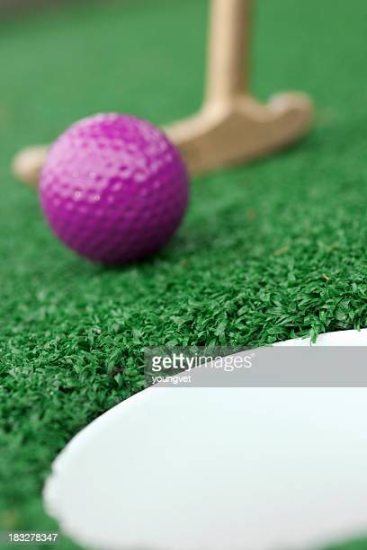 Purple golf ball being putted for miniature golf