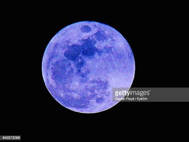 Purple Moon Glowing Against Black Sky