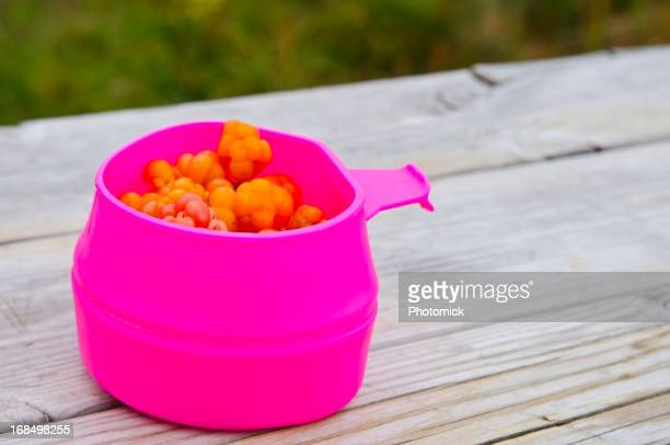 Purple mug with cloudberries on a wooden bench