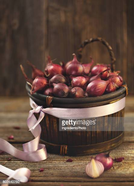 Purple onions in basket with a ribbon on wooden table.