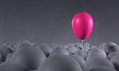 Bright purple pink party balloon emerging from a crowd of dark, gray anonymous balloons. Being special, standing out from the crowd, focusing on own individuality. Front view, looking up. Copy space o
