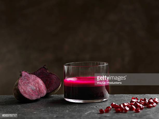 Purple raw beetroot and apple juice, halved beetroot and pomegranate seeds