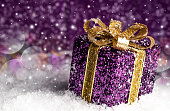 christmas purple shiny gift with a gold bow, on a snowy background