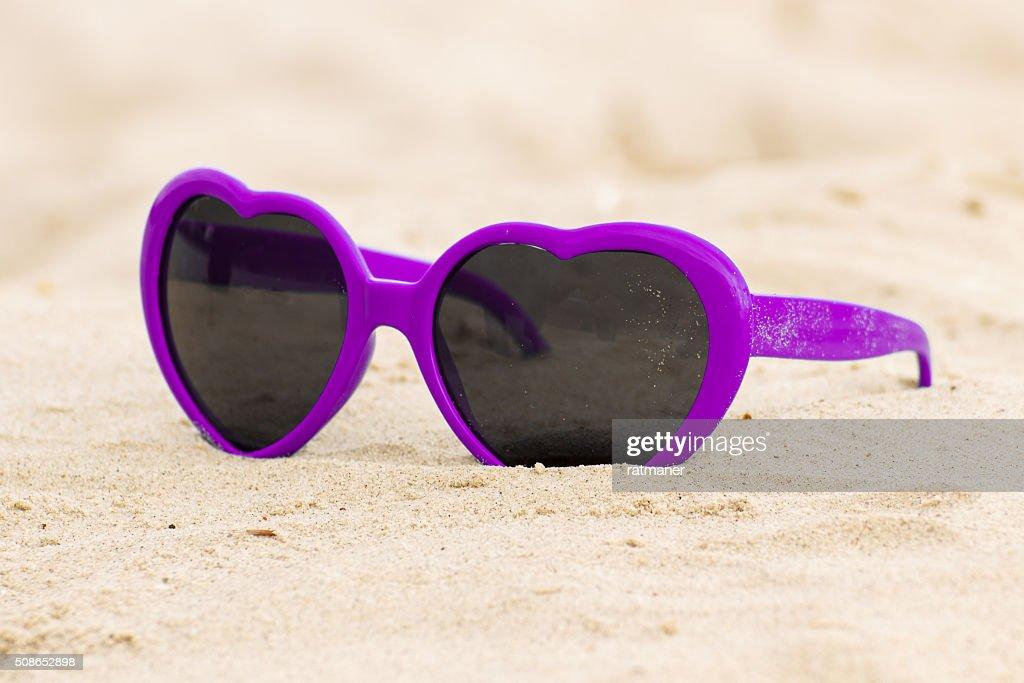 Purple sunglasses shaped heart on the sand : Stock Photo
