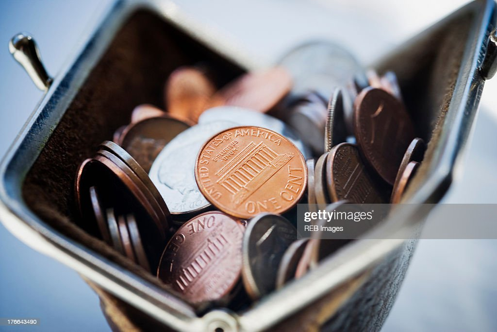 Purse filled with coins : Stock Photo