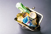 Wallet filled with many euro coins and banknotes