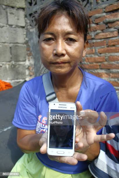Purwati and Subehi Monica's mother and young brother shows Monica's picture on the phone near Pasar Senen Station Central Jakarta on October 11 2017...
