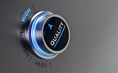 Push button on brushed metal surface. There is quality text and an arrow symbol on the button. The arrow is pointing high text on metal surface. Horizontal composition with copy space and selective fo