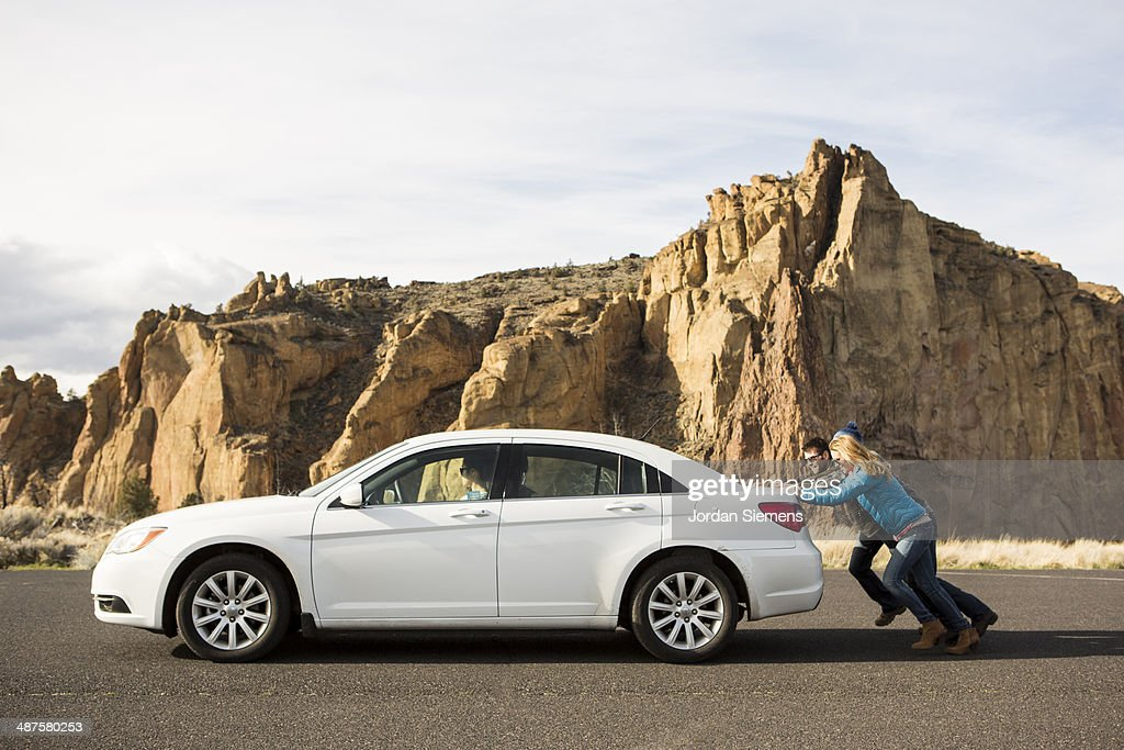 Pushing a broken down car.