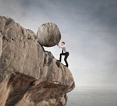 A man in a working suit pushing is illustrated to push the boulder