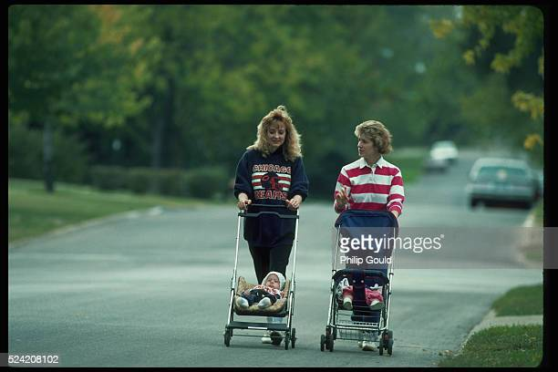 Pushing their babies in strollers two women chat as they walk down a neighborhood street in Normal Illinois