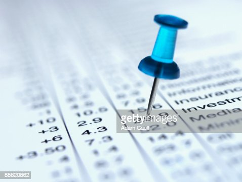 Pushpin in list of share prices : Stock Photo