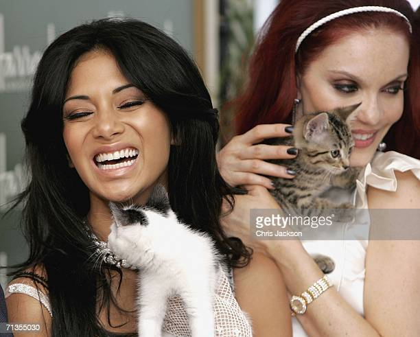 Pussy Cat Dolls Nicole Scherzinger and Carmit Bachar play with kittens as they open the Harrods Summer sale on July 3 2006 in London England