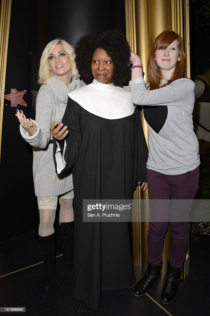 Pussycat Doll Kimberly Wyatt poses with a fan next to a wax figure of Whoopi Goldberg at Madame Tussauds on December 7, 2012 in London, England.