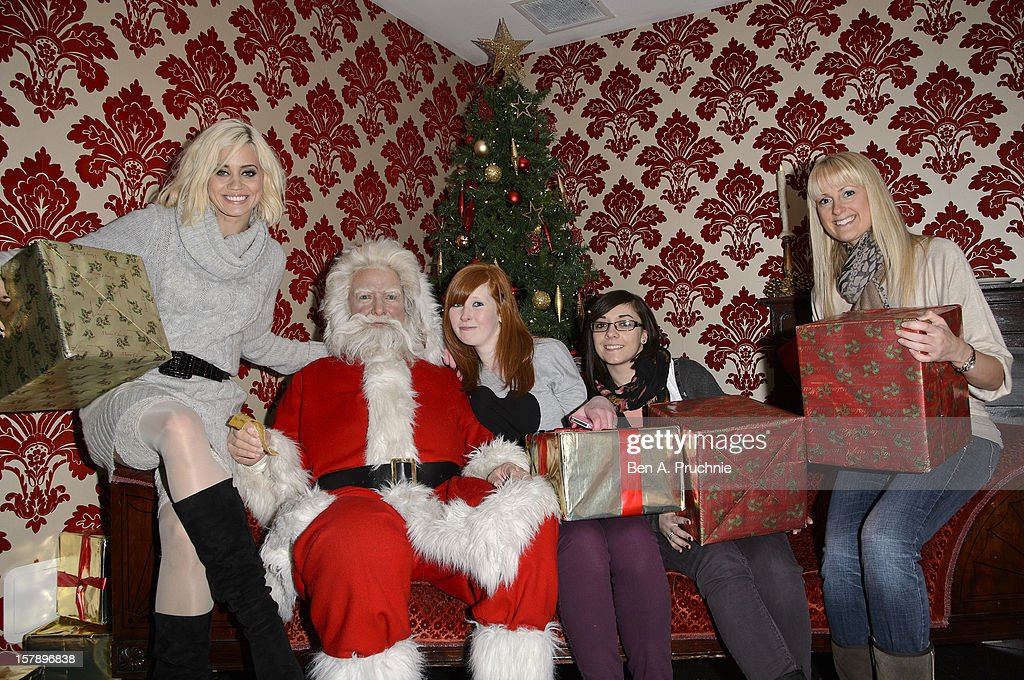 Pussycat Doll Kimberly Wyatt poses with fans next to a wax figure of Santa Claus at Madame Tussauds on December 7, 2012 in London, England.
